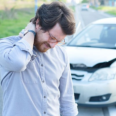 man in car accident holding neck